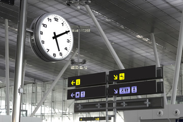Clock and signs at an airport