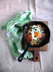 Shakshouka dish in tomato sauce with poached egg and spices