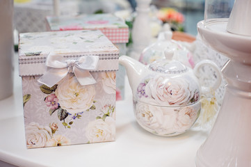 White teapot and a box with a picture of roses