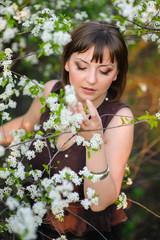 Beautiful girl walking in the spring blooming garden