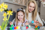 Happy mother and daughter painting easter eggs in living room
