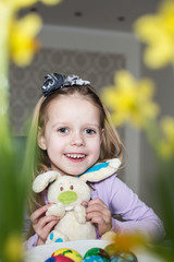 Smiling cute child with easter eggs and plush bunny