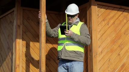 Engineer with a tape measure and tablet PC