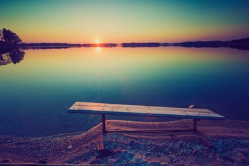 Vintage photo of bench on lake shore at sunset