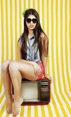 Fashion woman sitting on a tv