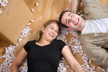Moving: Couple Laying On Floor Amid Packing Peanuts