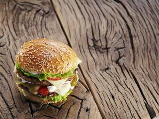Hamburger on old wooden table.