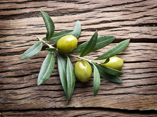 Olive twigs on old wooden table.