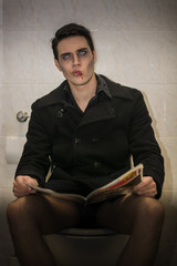 Male Vampire Sitting on a Toilet with Magazine