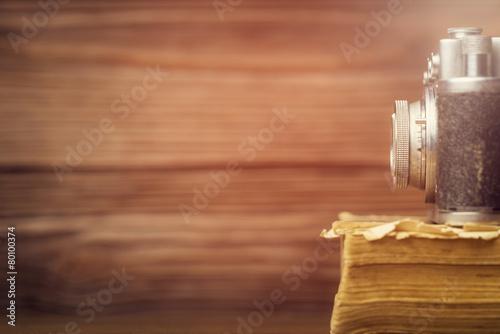 Retro camera on old book over wooden defocused background.