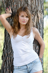 Lady against tree, she is wearing shorts and blouse