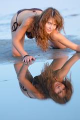 Woman in bikini mirroring in water