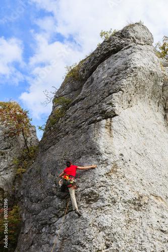 Rock climber on limestone rock near Krakow, Poland - 80102196