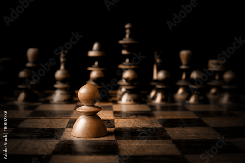 Fotografiet Chess. White pawn against all black.
