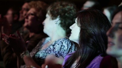Attractive young woman applauds a movie.  Focus on her with a small dolly move and projections on her face.