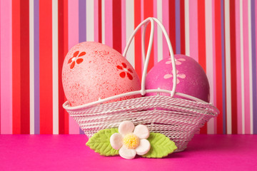 Pink and crimson Easter eggs in a basket with white flower