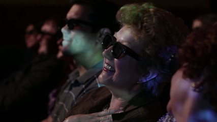 Mature woman watching a movie and wearing 3D glasses.  Focus on her with a small dolly move and projections on her face.