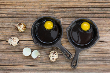 Raw eggs in frying pan, quail eggs, on wooden background