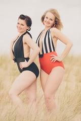Two Beautiful Young Women in Retro Vintage Swimsuits at Beach