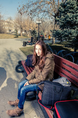 Young female passenger resting on park bench with her travel