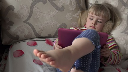 Smart Little Girl Using Tablet Computer while Sitting on Couch.