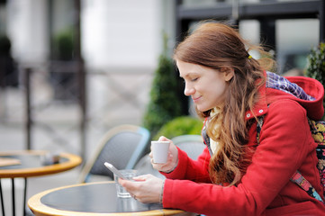 Young woman drinking coffee and using her smart phone