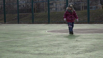 Sports Kid. Girl Playing Football. Baby with Ball on Sports Fiel