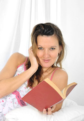 young attractive woman in nightgown on bed reading novel book