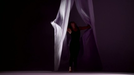 Gymnastic young woman dances with silks, runs towards camera.  Wide shot in studio with dark background.