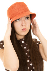 Cute teen girl model adjusting her orange hat wearing polka dot