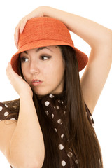 Teen model wearing orange hat looking away hand on her hat