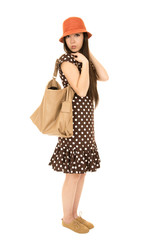 Cute teen girl standing wearing polka dot dress with a brown pur