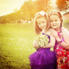 Two cute blonde little girls in park in spring