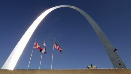 Gateway Arch in the city of St Louis, USA, with flags waving.