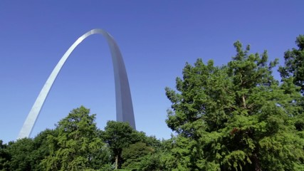 Tilt up to from trees to the massive Gateway Arch in the city of St Louis, USA.