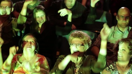 Theater audience breaks out into spontaneous dance routine.  Camera moves on a jib and moving images are projected on the people.