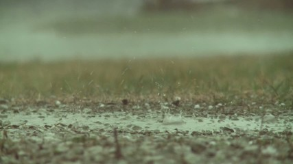 Big drops of rain hitting the ground and splashing during a storm.  Two clips, recorded in slow motion at 60fps.