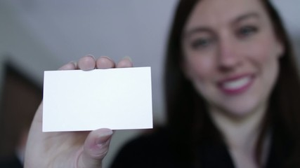 Young woman holds up a blank business card to the camera.  If last frame is frozen, various text or graphics can be added to the card.  Camera mounted on moving jib arm.