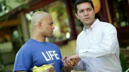 "Man in a blue T-shirt that says ""LIFE"" sells a lemon to a shady character on the street."