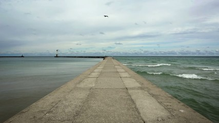 Concrete pier with calm water on one side and waves breaking on the other.  Lighthouse can be seen at the end of the harbor.  Recorded on Lake Michigan at Frankfort, Michigan.