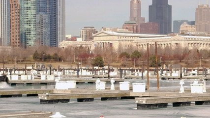Boat breaking through ice in harbor along shoreline of Chicago