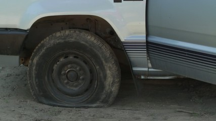 Driver discovers he has a flat tire, gets out of his truck and calls for roadside assistance.