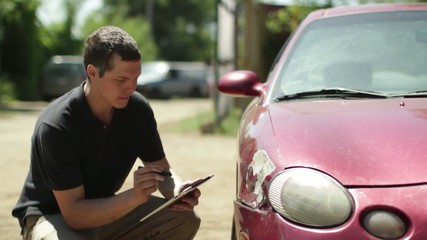 Insurance person inspects the damage on a car and makes notes on a digital tablet.