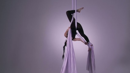 Athletic young woman supports herself in two inverted poses while doing aerial yoga.  Wide shot on neutral background with lilac tint.