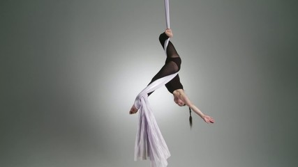 Athletic young woman suspends herself upside down while doing aerial yoga.  Wide shot on neutral background.