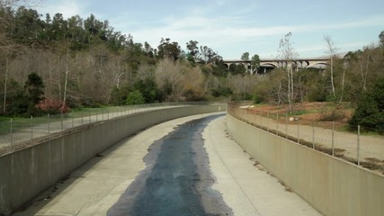 This small stream in a concrete canyon is actually part of the Los Angeles River.  Two clips looking in different directions between the cities of Echo Park and Pasadena, Los Angeles, California.