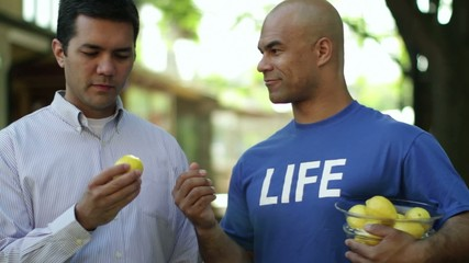 """Man in a blue T-shirt that says """"LIFE"""" hands lemons to people on the street.  Man takes one and it changes (jump cut) to a jug of fruit punch."""
