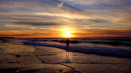 Fishermen at the beach fishing at sunset