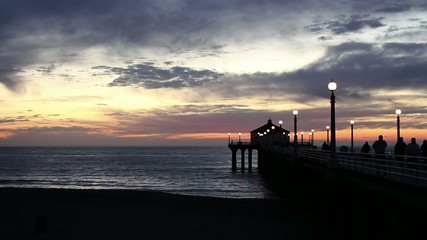 Beautiful sunset over Manhattan Beach in Los Angeles, California, USA, with silhouetted people walking on the pier. Two clips.