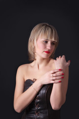 Attractive blond woman on studio dark background